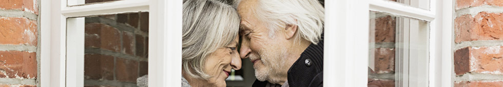 Older couple smiling in front of window
